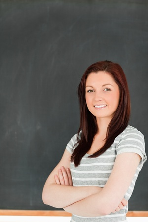 Portrait of a cute woman standing in front of a blackboard in a classroom photo