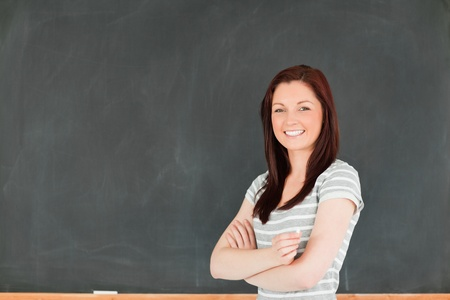 high schools: Bella mujer de pie frente a una pizarra en un aula