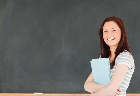 high schools: Joven mujer sosteniendo sus notas en un aula