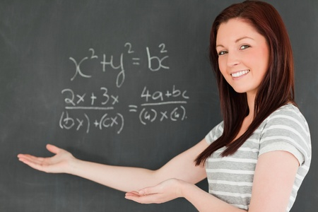 Beautiful young woman showing an equation on a blackboard in a classroom photo