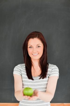 Portrait of a cute redhead against a blackboard in a classroom photo