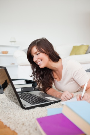 Young beautiful woman relaxing with her laptop and posing while writing on a notebook in the living room photo