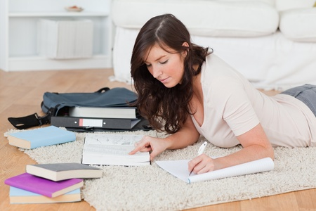 Young brunette female writing on a notebook while lying on a carpet in the living room photo