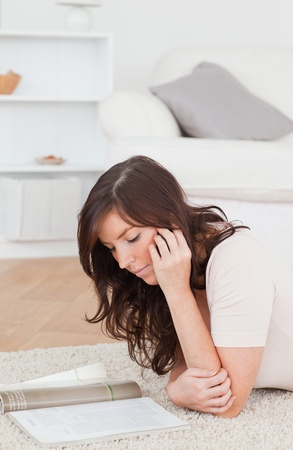 Young gorgeous female reading a magazine while lying on a carpet in the living room photo