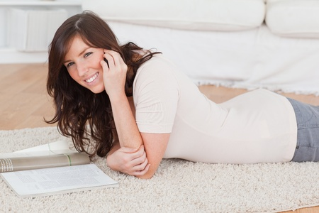 Young beautiful woman reading a magazine while lying on a carpet in the living room photo