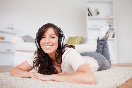 Good looking brunette female using headphones while lying on a carpet in the living room photo