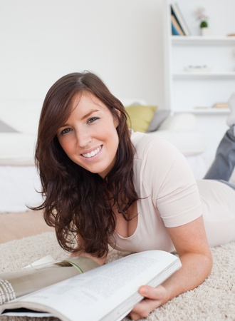 adult magazine: Beautiful woman reading a magazine while lying on a carpet in the living room