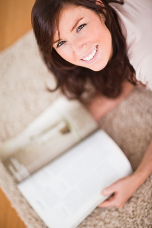 Cute woman reading a magazine while lying on a carpet in the living room photo