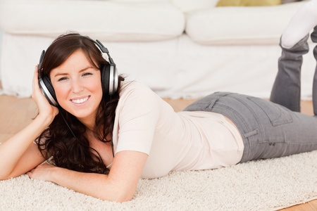 Beautiful brunette woman using headphones while lying on a carpet in the living room Stock Photo - 10220253