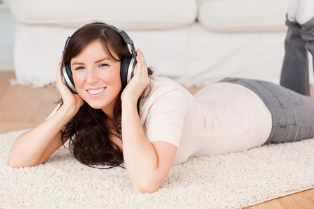 Attractive brunette woman using headphones while lying on a carpet in the living room photo