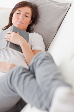 Young attractive female having a rest and reading a book while lying on a sofa in the living room Stock Photo - 10220443
