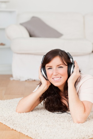 Gorgeous brunette woman using headphones while lying on a carpet in the living room photo