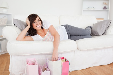 Young gorgeous female posing with her shopping bags while lying on a sofa in the living room photo