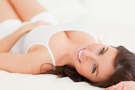 Gorgeous brunette female posing while lying on a bed photo