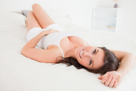 beautiful bed: Beautiful brunette female posing while lying on a bed