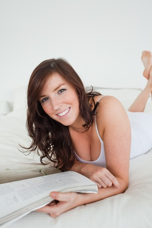 Beautiful female reading a magazine while lying on a bed photo