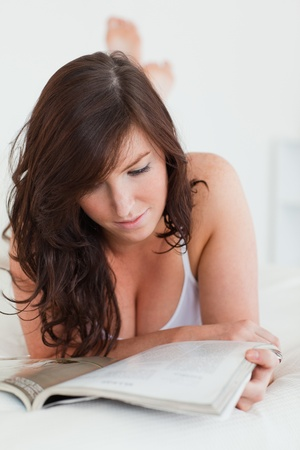 Lovely female reading a magazine while lying on a bed photo