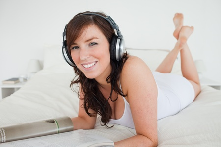 Lovely female with headphones reading a magazine while lying on a bed photo