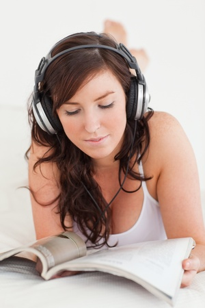 Attractive female with headphones reading a magazine while lying on a bed Stock Photo - 10220370