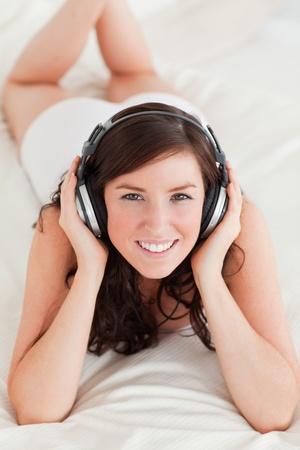 Good looking female with headphones lying on a bed photo