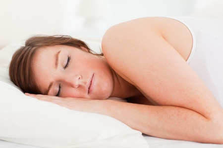 Gorgeous brunette female having a rest while lying on a bed photo
