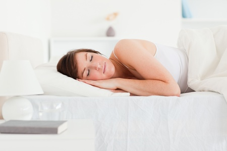 Lovely brunette woman having a rest while lying on a bed Stock Photo - 10217472