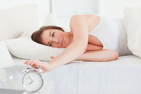 Lovely brunette woman turning off a clock while lying on a bed photo