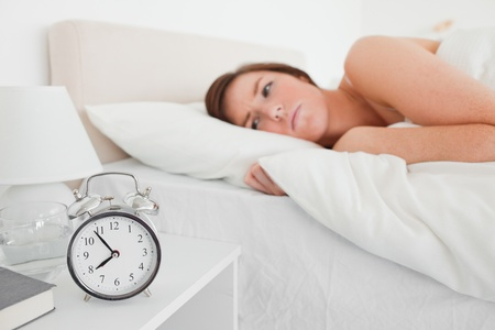 Lovely brunette woman awaking with a clock while lying on a bed Stock Photo - 10219207
