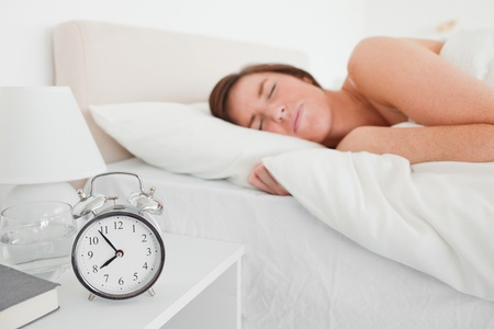 Charming brunette woman awaking with a clock while lying on a bed Stock Photo - 10219146