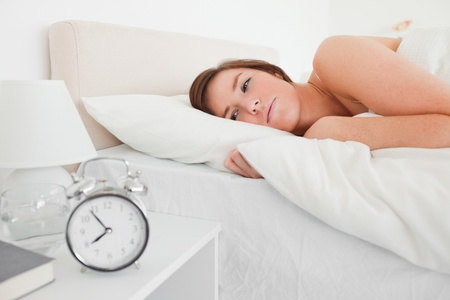 awaking: Beautiful brunette woman awaking with a clock while lying on a bed Stock Photo