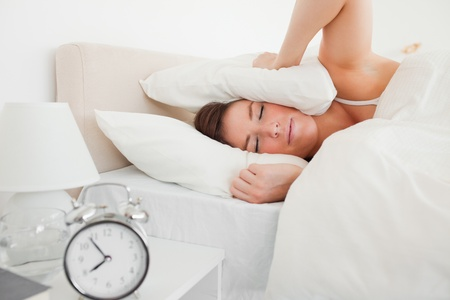awaking: Pretty brunette woman awaking with a clock while lying on a bed Stock Photo