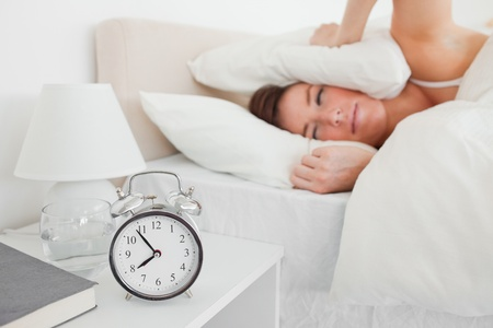 awaking: Attractive brunette woman awaking with a clock while lying on a bed