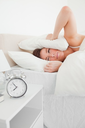 awaking: Good looking brunette woman awaking with a clock while lying on a bed Stock Photo