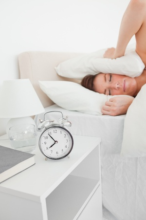 Cute brunette woman awaking with a clock while lying on a bed Stock Photo - 10217912