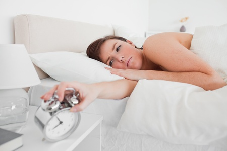 Gorgeous brunette female awaking with a clock while lying on a bed Stock Photo - 10219256