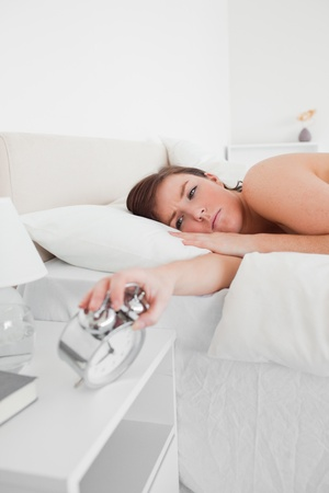 Attractive brunette female awaking with a clock while lying on a bed Stock Photo - 10217881