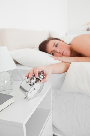 awaking: Good looking brunette female awaking with a clock while lying on a bed