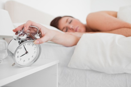 awaking: Charming brunette female awaking with a clock while lying on a bed