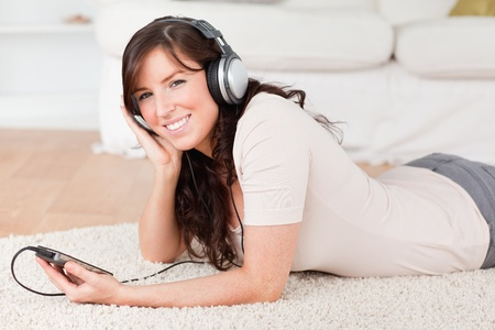 Attractive brunette female listening to music with her mp3 player while lying on a carpet in the living room photo