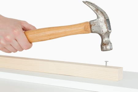 Hammer driving a nail into a wooden board against a white background Stock Photo
