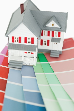 Close up of a maniature house and a color chart agaiinst a white background photo