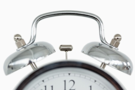 Close up of an old fashioned alarm clock against a white background photo