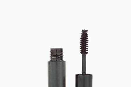 A tube and a brush of mascara against a white background photo