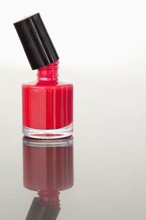 Portrait of an opened nail polish flask against a white background photo