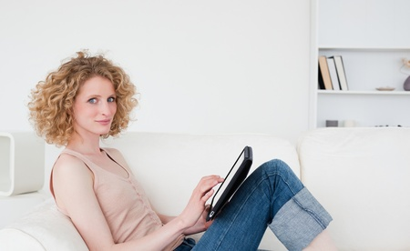 Beautiful blonde woman relaxing with her tablet while sitting on a sofa in her appartment photo
