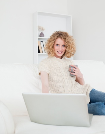Lovely blonde woman relaxing with her laptop while sitting on a sofa in her appartment photo
