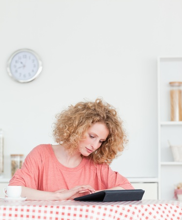 Charming blonde woman relaxing with her tablet while sitting in the kitchen in her appartment photo