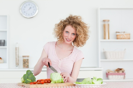 Pretty blonde woman cooking some vegetables in the kitchen in her appartment photo