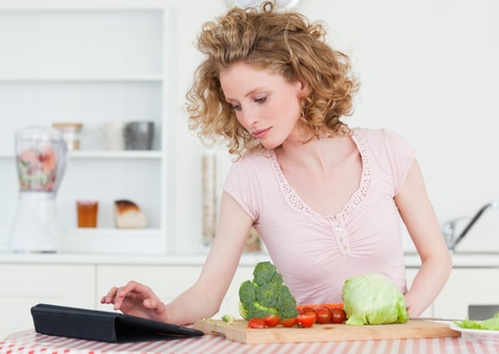 Pretty blonde woman relaxing with her tablet while cooking some vegetables in the kitchen in her appartment photo