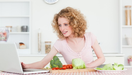 Good looking blonde woman relaxing with her laptop while cooking some vegetables in the kitchen in her appartment photo